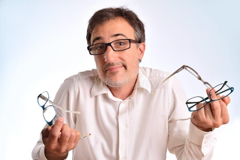 Okulistyczny biznesowy mężczyzna wzrusza ramionami ramiona z kilka eyeglasses obrazy stock