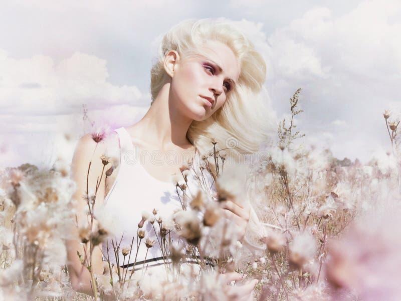 Okwitnięcie. Piękno blondynka w Wietrznym polu z kwiatami. Natura. Wiosna zdjęcia royalty free