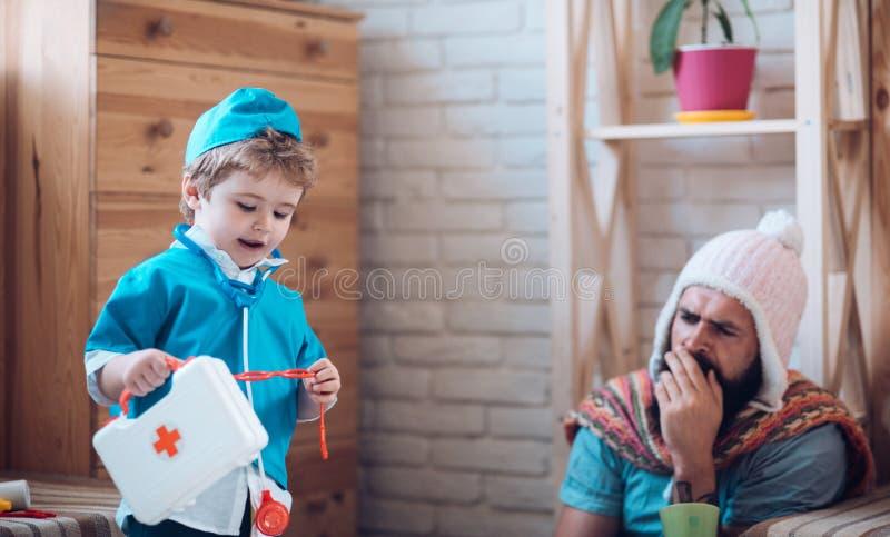 Olá! eu sou seu doutor O filho com a caixa dos primeiros socorros toma do pai em casa Pouco doutor da brincadeira com homem Menin fotos de stock royalty free