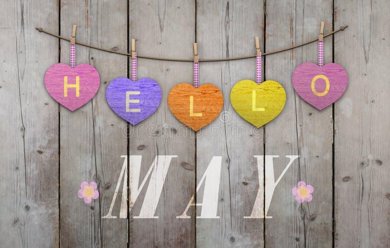 Olá! maio escrito no rosa de suspensão e corações alaranjados e roxos e fundo de madeira resistido fotografia de stock