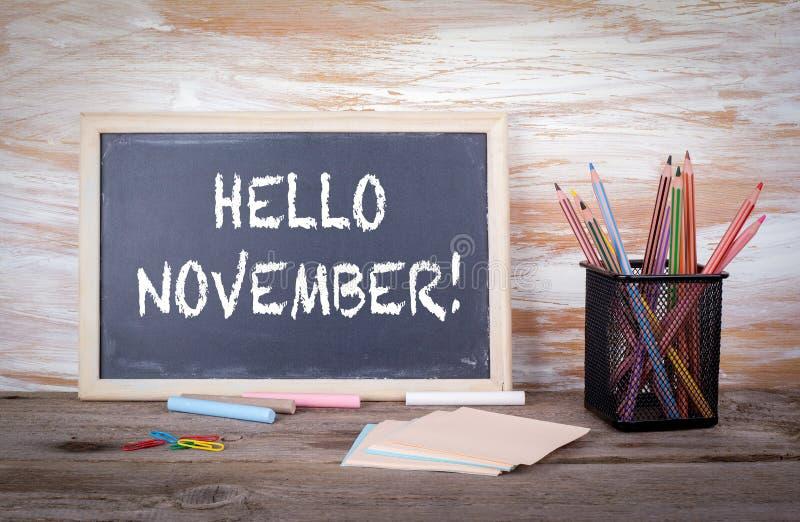 Olá! novembro! Texto em um quadro-negro Tabela de madeira velha com texto fotografia de stock royalty free
