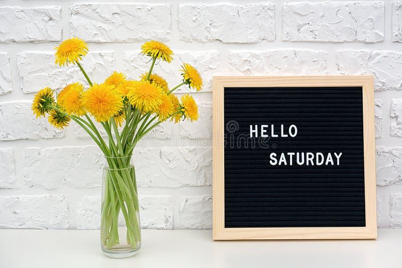 Olá! palavras de sábado na placa da letra preta e no ramalhete de flores amarelas dos dentes-de-leão na tabela contra a parede de fotografia de stock royalty free