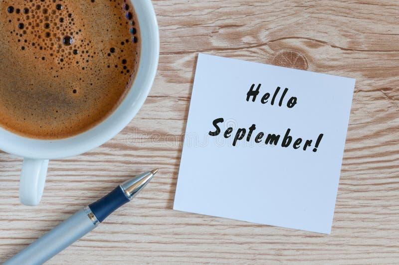 Olá! setembro escreveu na etiqueta de papel com café e na pena no fundo de madeira fotografia de stock