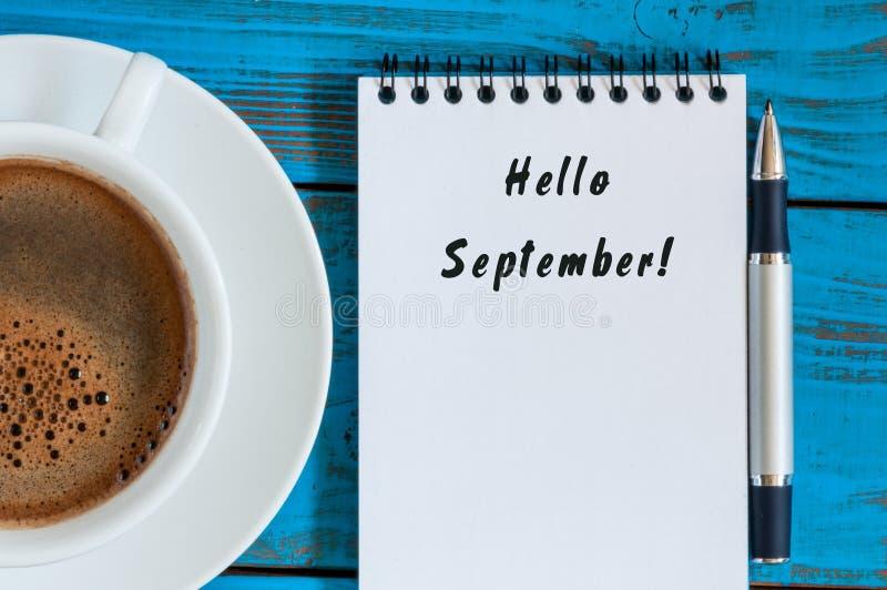 Olá! setembro escreveu no bloco de notas de papel no fundo de madeira azul com o copo do café da manhã Vista superior foto de stock royalty free