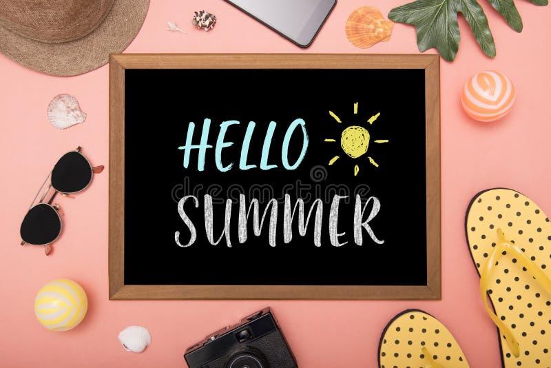 Olá! texto do verão na configuração preta e no viajante do plano da placa fotografia de stock royalty free