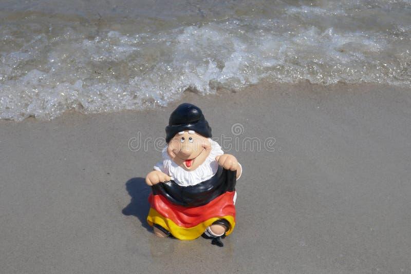 Olá! verão! O gnomo engraçado do jardim com uma bandeira de Alemanha senta-se felizmente em uma pilha da areia na praia com o mar fotos de stock royalty free