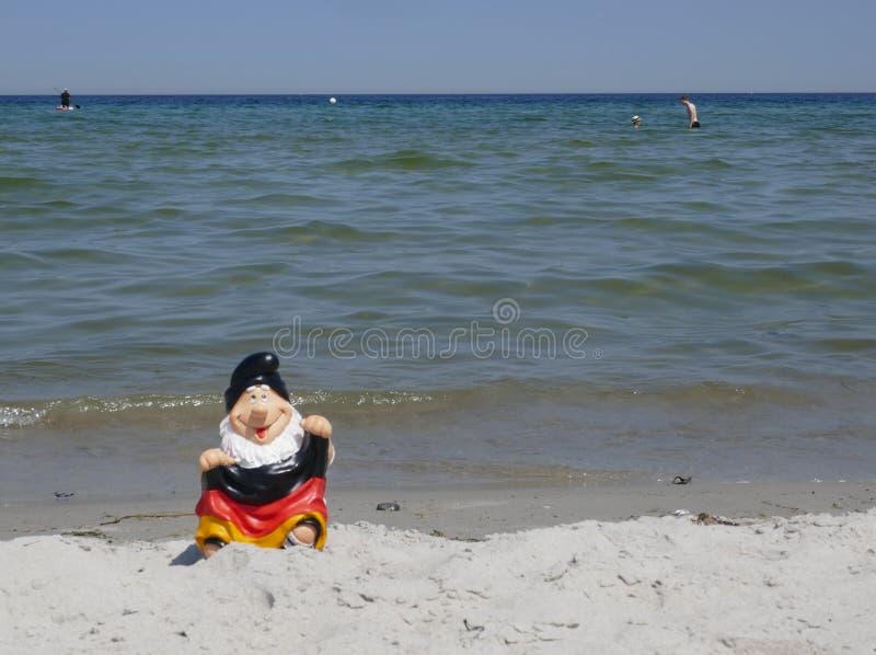 Olá! verão! O gnomo engraçado do jardim com uma bandeira de Alemanha senta-se felizmente em uma pilha da areia na praia com o mar fotos de stock