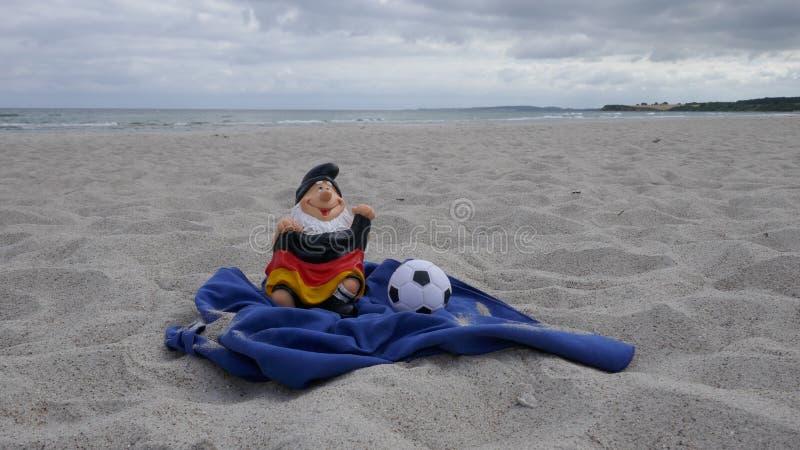 Olá! verão! O gnomo engraçado do jardim com uma bandeira e um futebol senta-se felizmente em uma pilha da areia na praia com o ma foto de stock