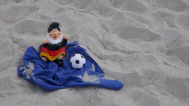 Olá! verão! Um gnomo engraçado do jardim com uma bandeira e um futebol senta-se felizmente em uma pilha da areia na praia fotografia de stock