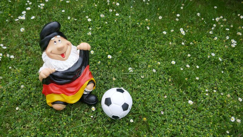 Olá! verão! Um gnomo engraçado do jardim com uma bandeira e um futebol senta-se felizmente em um prado verde fotografia de stock