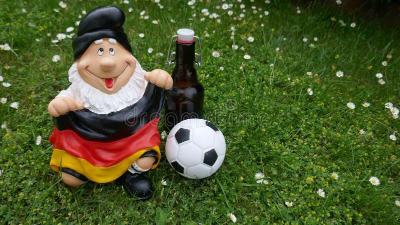 Olá! verão! Um gnomo engraçado do jardim com uma bandeira, um futebol e uma garrafa da cerveja senta-se felizmente em um prado ve foto de stock royalty free