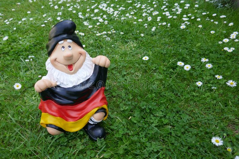 Olá! verão! Um gnomo engraçado do jardim com uma bandeira senta-se felizmente em um prado verde imagem de stock