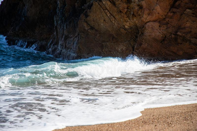 Ola oceánica cerca de la roca de la playa foto de archivo
