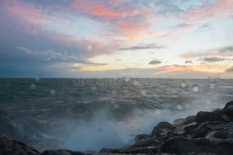 Ola oceánica que salpica dramática por la tarde con el cielo crepuscular en invierno en el rompeolas en el embarcadero del St Kil fotos de archivo libres de regalías