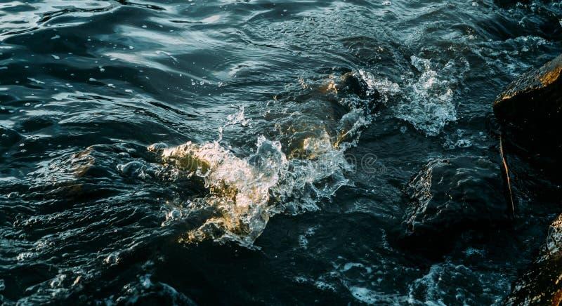 Olas de agua de mar salpicadas de rocas imagen de archivo libre de regalías