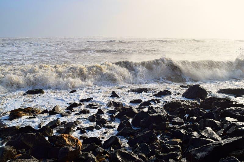 Olas marítimas durante la alta marea en la costa rocosa en el soleado día con el océano infinito - fondo natural del paisaje ma imagen de archivo libre de regalías
