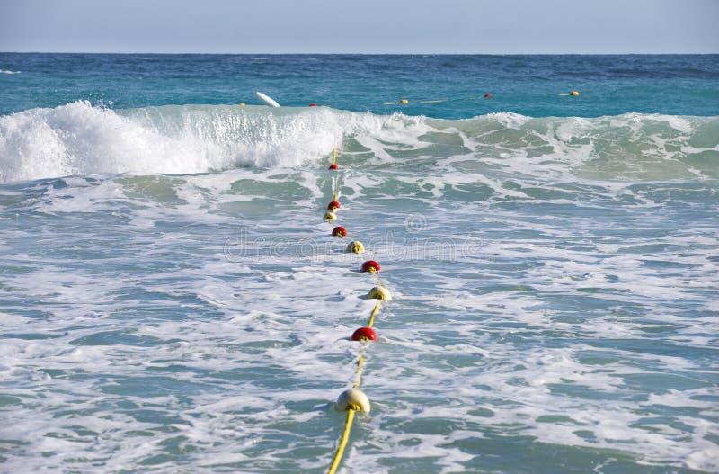 Olas oceánicas y boyas coloridas en una cuerda amarilla fotografía de archivo libre de regalías