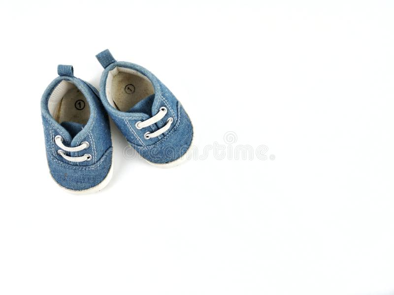 old second hand blue shoes or sneakers for kids or baby on white background with copy space royalty free stock image