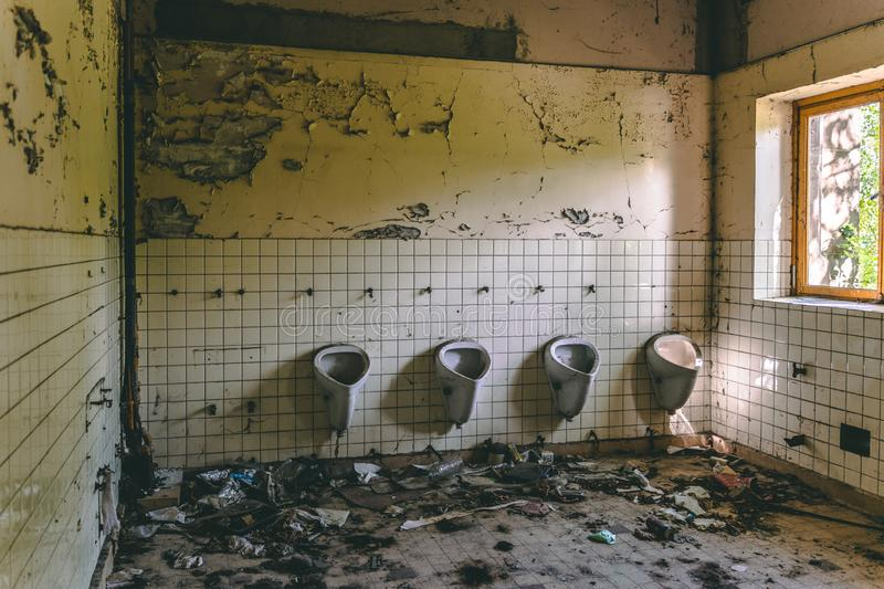 Old abandoned bathroom in a school stock image