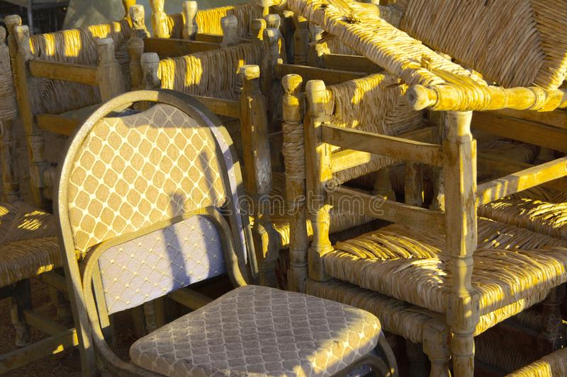 Old abandoned beach furniture on an empty seashore against a background of yellow sand and blue sky. Thrown, unnecessary things. Vacation, tourism royalty free stock images