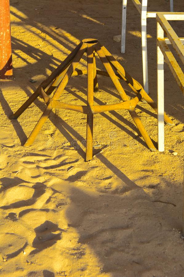Old abandoned beach furniture on an empty seashore against a background of yellow sand and blue sky. Thrown, unnecessary things. Vacation, tourism royalty free stock image
