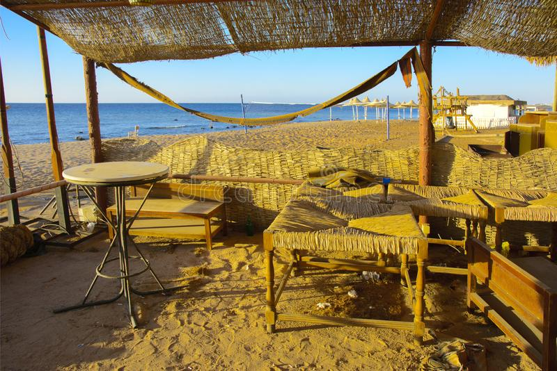 Old abandoned beach furniture on an empty seashore against a bac. Kground of yellow sand and blue sky. Thrown, unnecessary things. Vacation, tourism royalty free stock photos