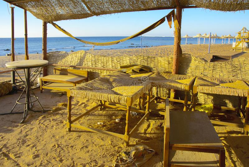 Old abandoned beach furniture on an empty seashore against a bac. Kground of yellow sand and blue sky. Thrown, unnecessary things. Vacation, tourism stock photos