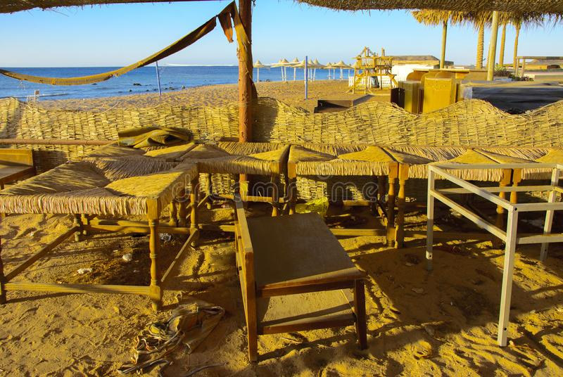 Old abandoned beach furniture on an empty seashore against a bac. Kground of yellow sand and blue sky. Thrown, unnecessary things. Vacation, tourism royalty free stock photo