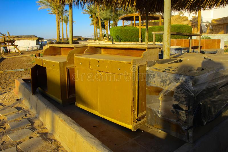 Old abandoned beach furniture on an empty seashore against a background of yellow sand and blue sky. Thrown, unnecessary things. Vacation, tourism royalty free stock photography