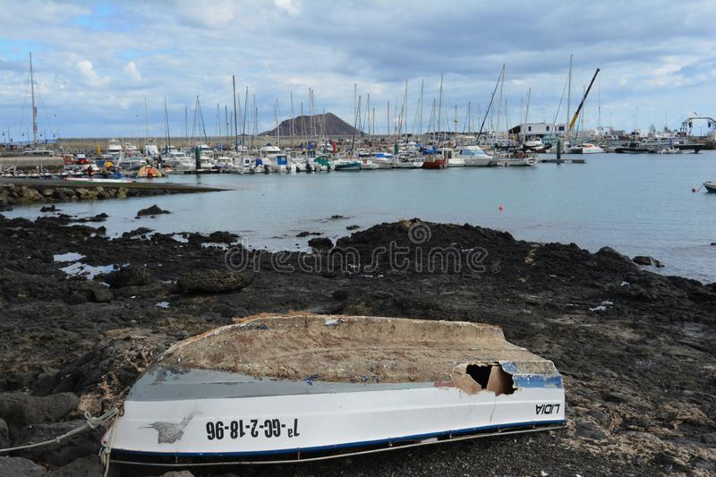 Old abandoned boat on the coast. Yacht pier at the background Corralejo, Fuerteventura, Spain stock photos