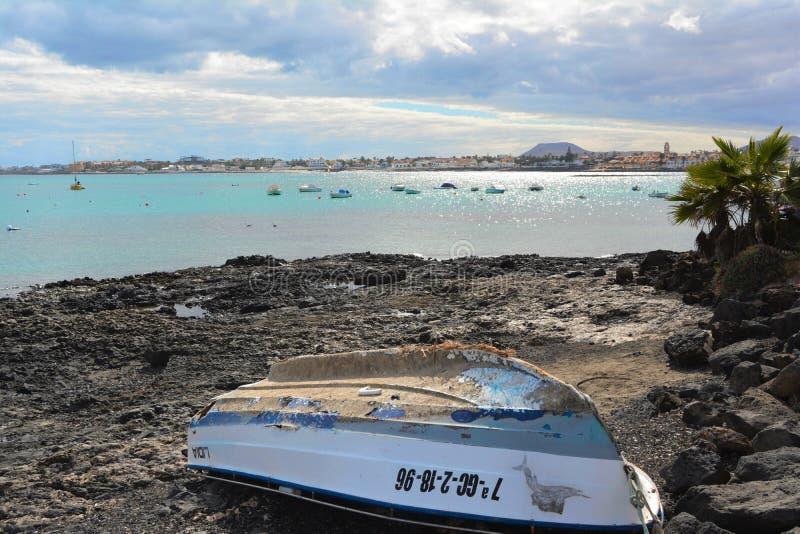 Old abandoned boat on the rocky coast of Corralejo, Fuerteventura, Spain. royalty free stock image