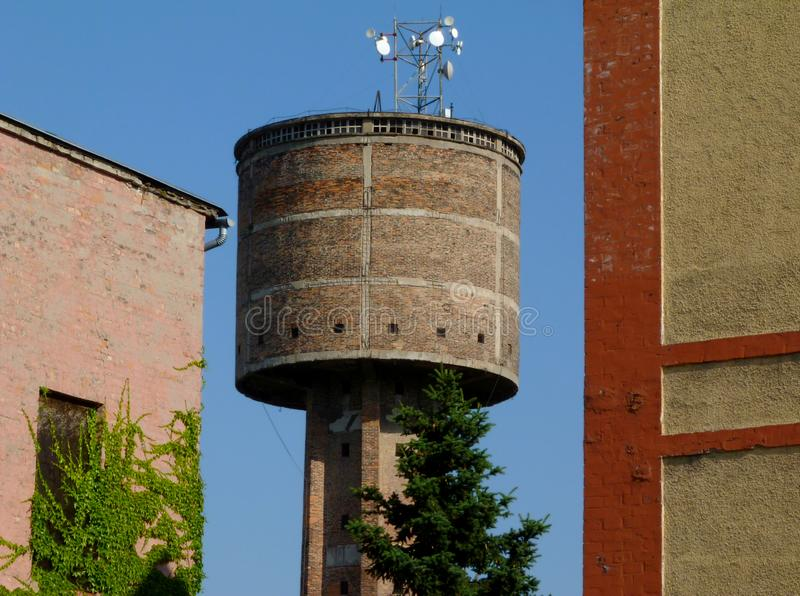 Old abandoned brick water tower detail with radio transmission antenna on top stock photo