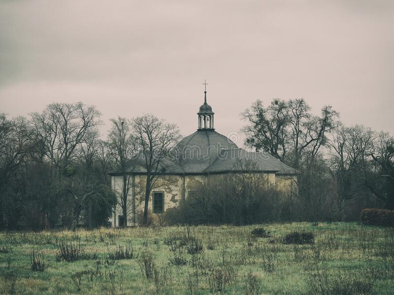 Old abandoned church. Between bare trees royalty free stock images