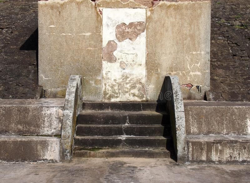 Old abandoned concrete shelter with a blocked door with cracked repaired steps and patched eroded walls in sunlight and shadow stock photo