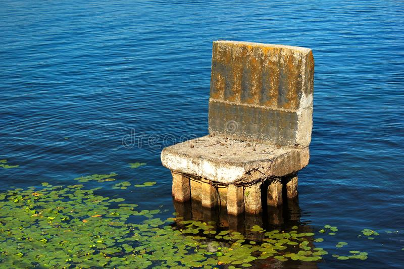 Old abandoned concrete support of a bridge looks like a chair in water stock photography
