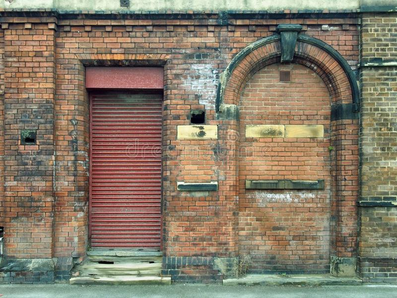 Old abandoned derelict industrial premises with bricked up door stock photography