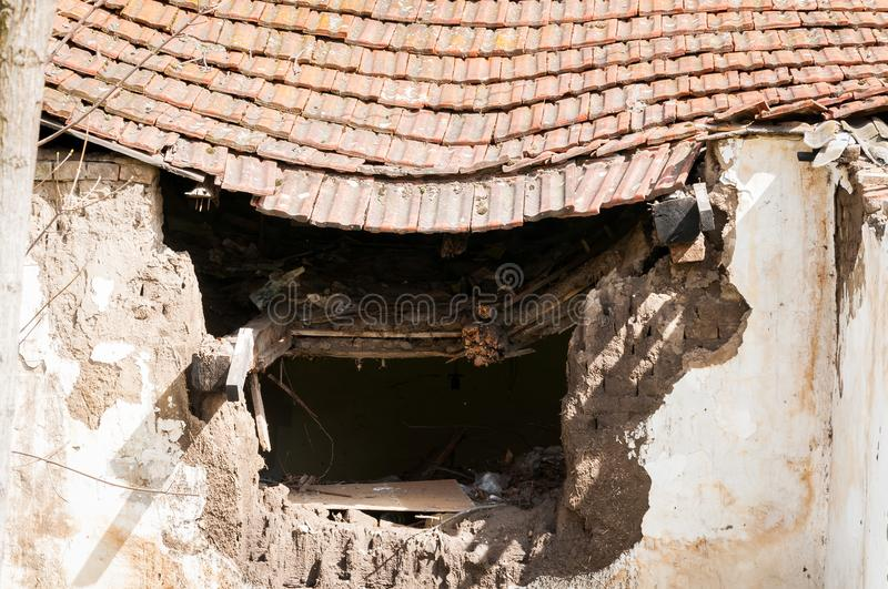 Old abandoned house collapsed roof with damaged vintage tiles after natural disaster of earthquake or hurricane stock photos