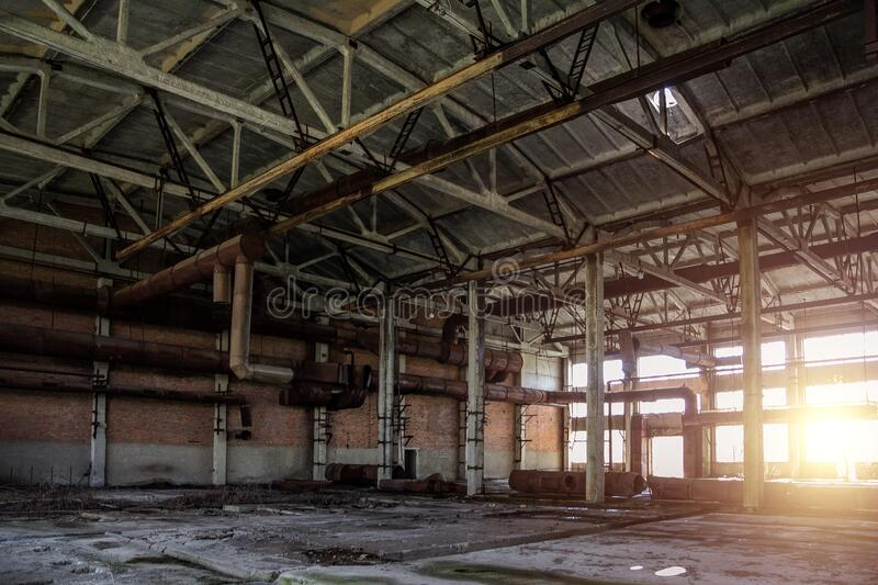 Old abandoned industrial building with rusty remnants of pipeline.  royalty free stock image