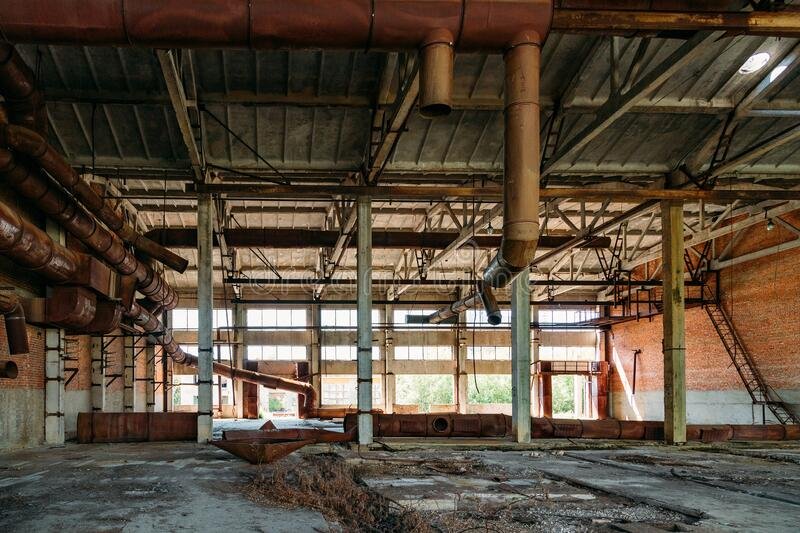 Old abandoned industrial building with rusty remnants of pipeline.  stock photography