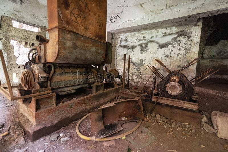 Old abandoned industrial machine tools and rusty metal equipment in abandoned factory. Old abandoned industrial machine tools and rusty metal equipment in stock photography