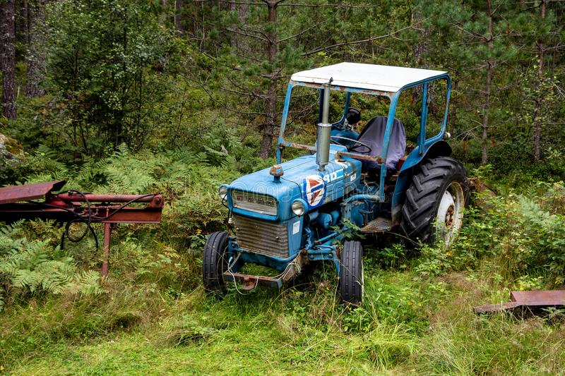 Old abandoned and overgron blue Ford tractor stock photo