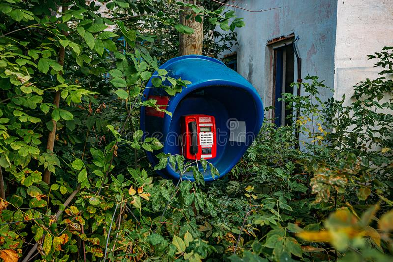 Old abandoned overgrown phone booth. In abandoned village stock photography