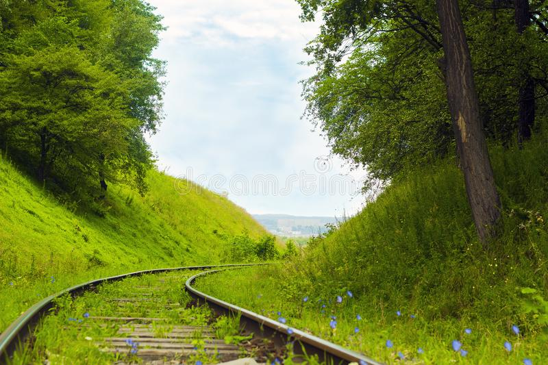 Old abandoned railroad among forested hills. Railway on country road. Rails among trees royalty free stock images