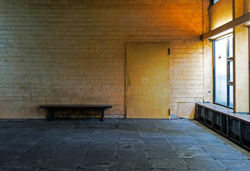 Old abandoned room with bench and a door royalty free stock photos