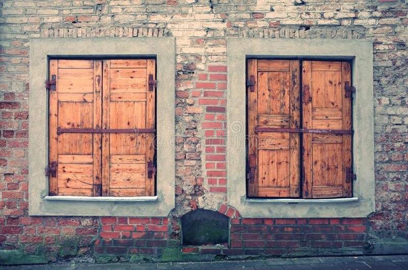 Old abandoned rustic brick wall with closed wooden windows. Background for photographers or designers royalty free stock photo