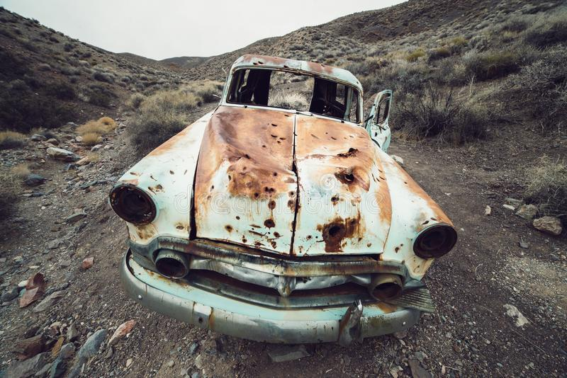 OLd abandoned rusty retro car in the desert with bullet holes in metal. stock images