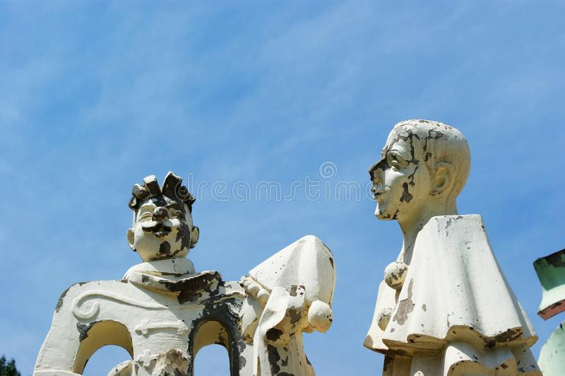 Old abandoned sculptures of clowns with peeling paint stock images