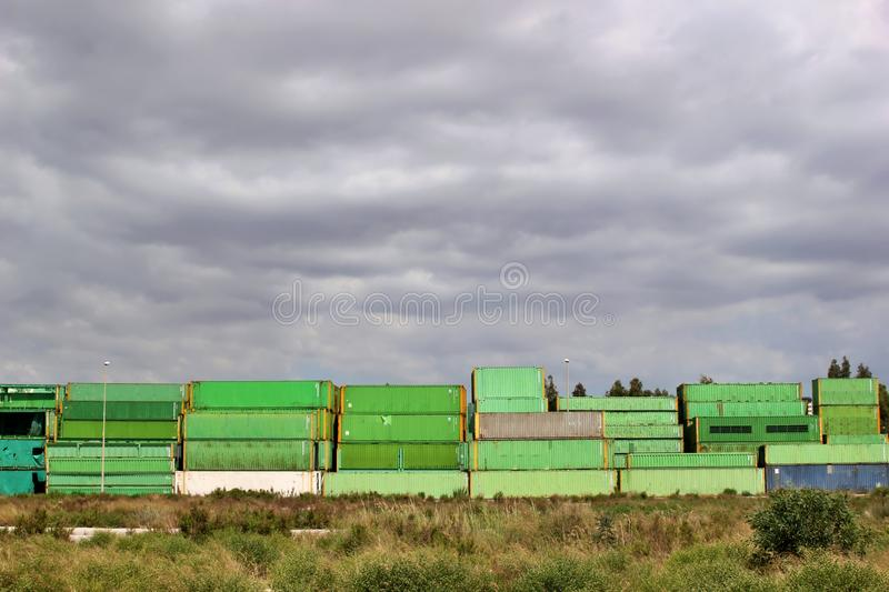 Old abandoned shipping containers stacked in an open field stock photos