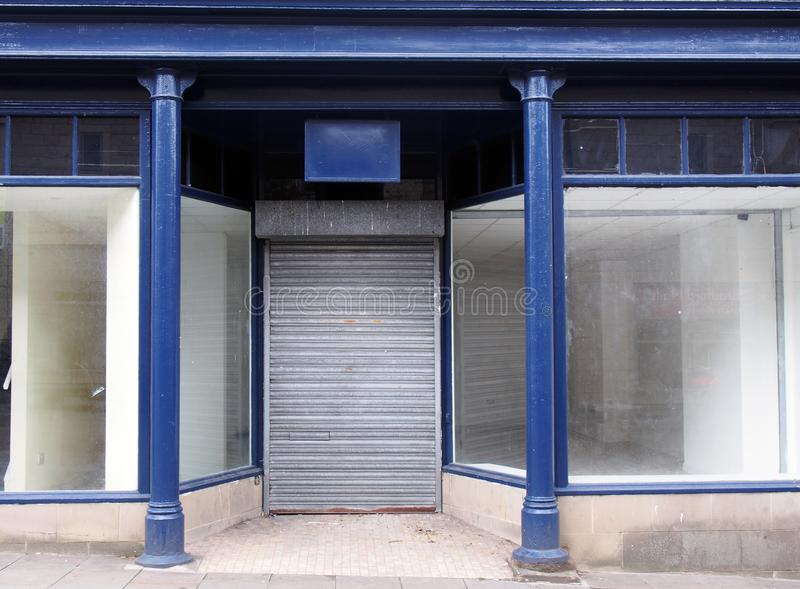 Old abandoned shop painted blue and white with empty store front dirty windows and closed shutters on the door. The facade of an old abandoned shop painted blue stock photo
