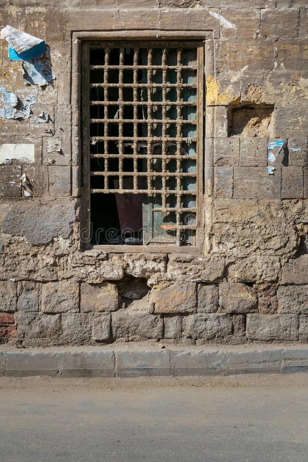 Old abandoned stone bricks wall with one closed grunge broken wooden window covered by wooden grid. Dard El Ahmar district, Cairo, Egypt stock photos